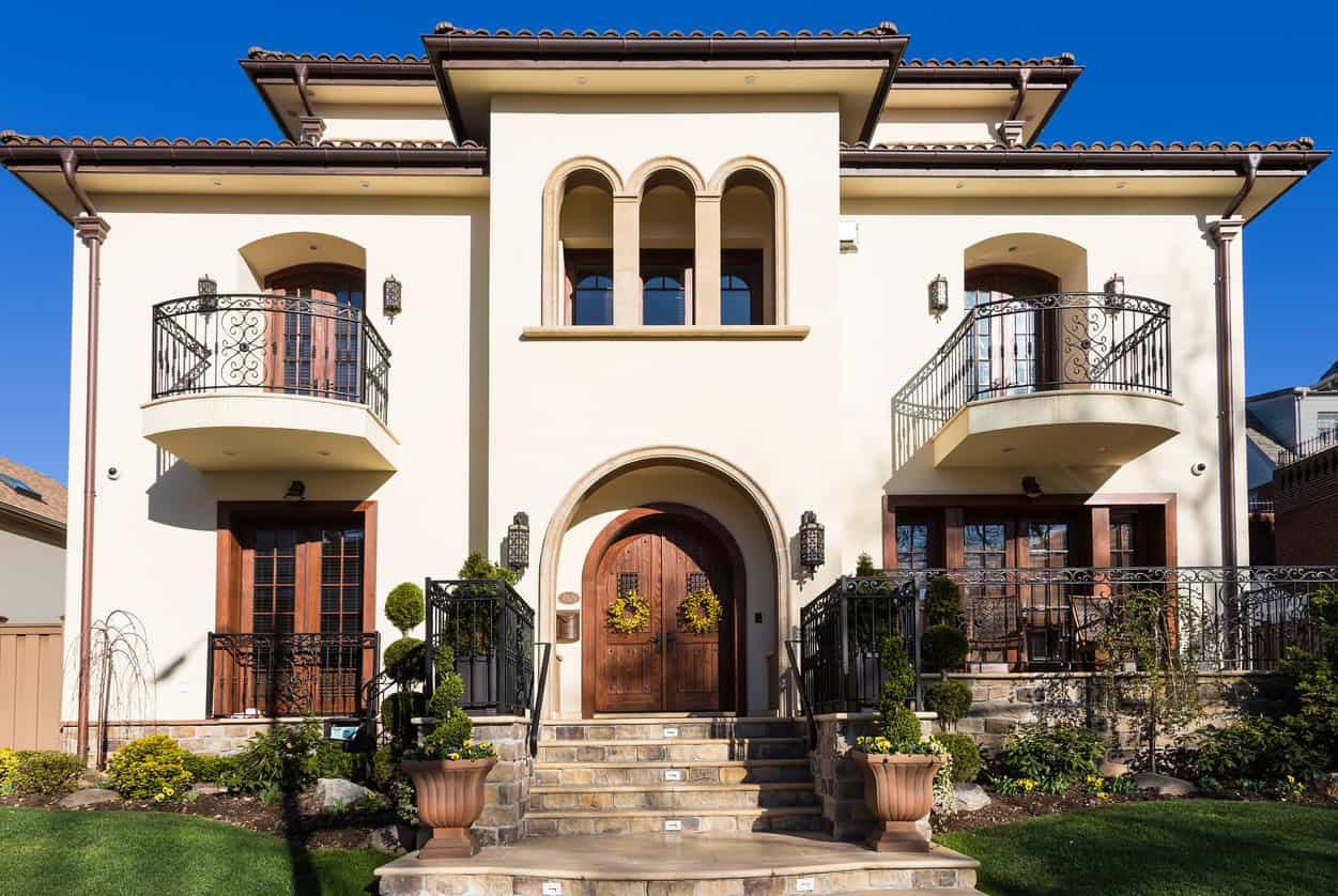 Luxury house with bedroom balconies under arches and an arched foyer with steps for a grand entrance.