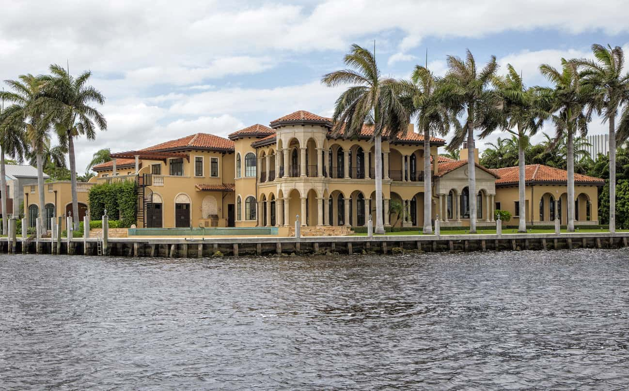 Warm yellow luxury waterfront house with arched windows surrounded by palm trees.