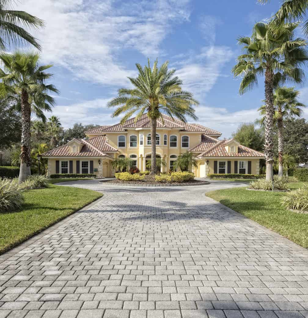 Exterior view of a beautiful estate home with paver driveway.