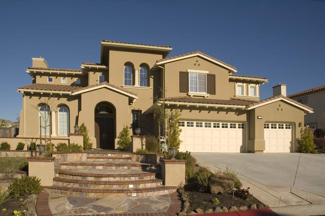 Executive home in Northern California with an arched foyer and windows, exterior steps leading to the entrance and a large garage and concrete driveway.
