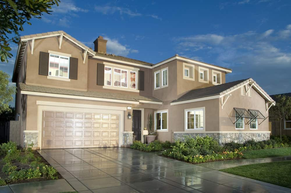Two-story suburban house with cement driveway.