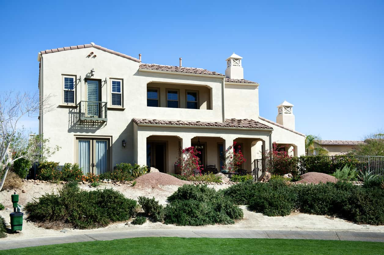 Stucco house shines brightly under a clear blue sky.