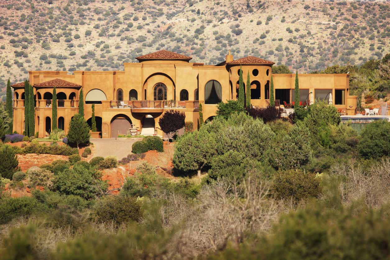 Huge luxury stucco home featuring geographic windows and tucked in a desert landscape surrounded by green plants.