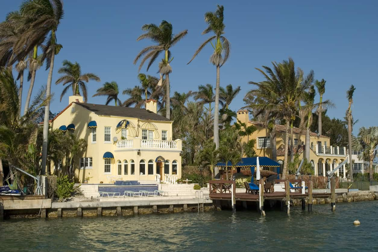 Two-story luxury waterfront home surrounded by tall palm trees.#