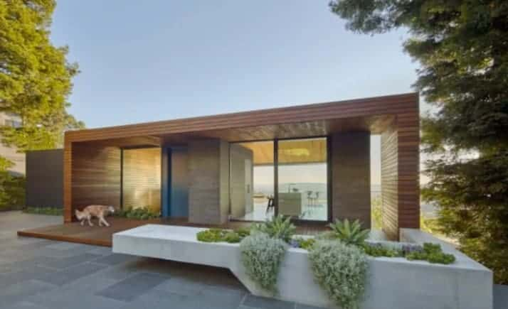 A stunning house with a wooden exterior. It features a spacious courtyard with nice plants and trees.