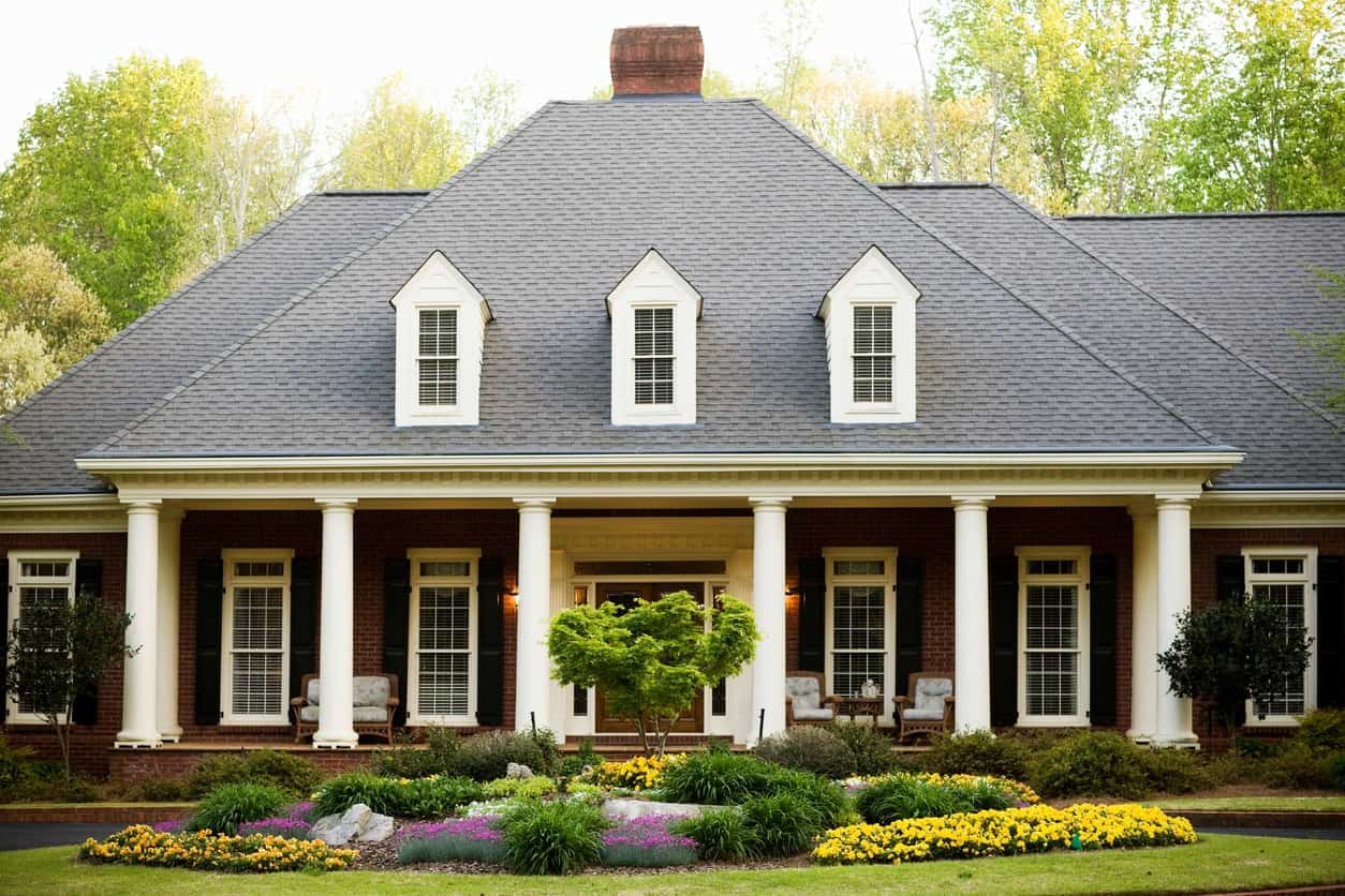 This house looks massive and heavy because of its dark roofing and dark brick exterior. White windows and columns offset with cool tones.