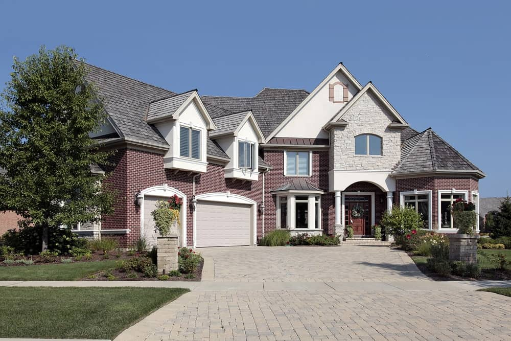 Multilevel suburban brick house with spacious brick driveway and double garage.
