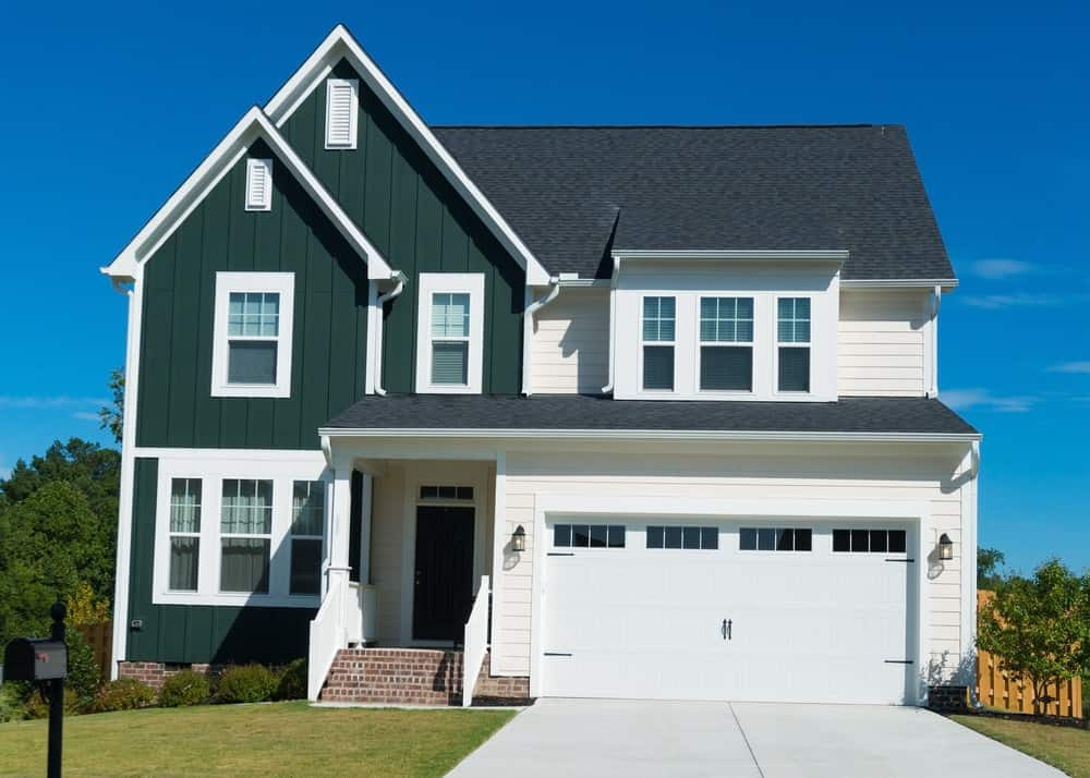 Bright white trims emphasize the house's height and complement the dark green exterior siding. A coating of cool beige on the exterior walls, however, recedes together with the crisp white trims.