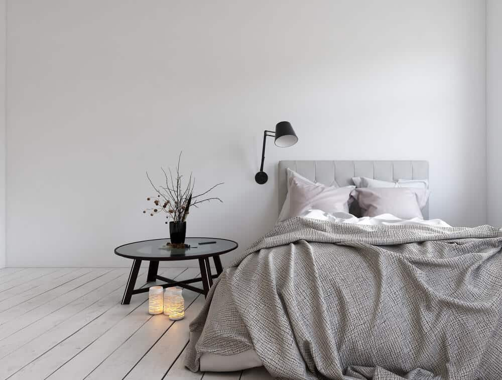 A black swing arm lighting in a minimalist bedroom.