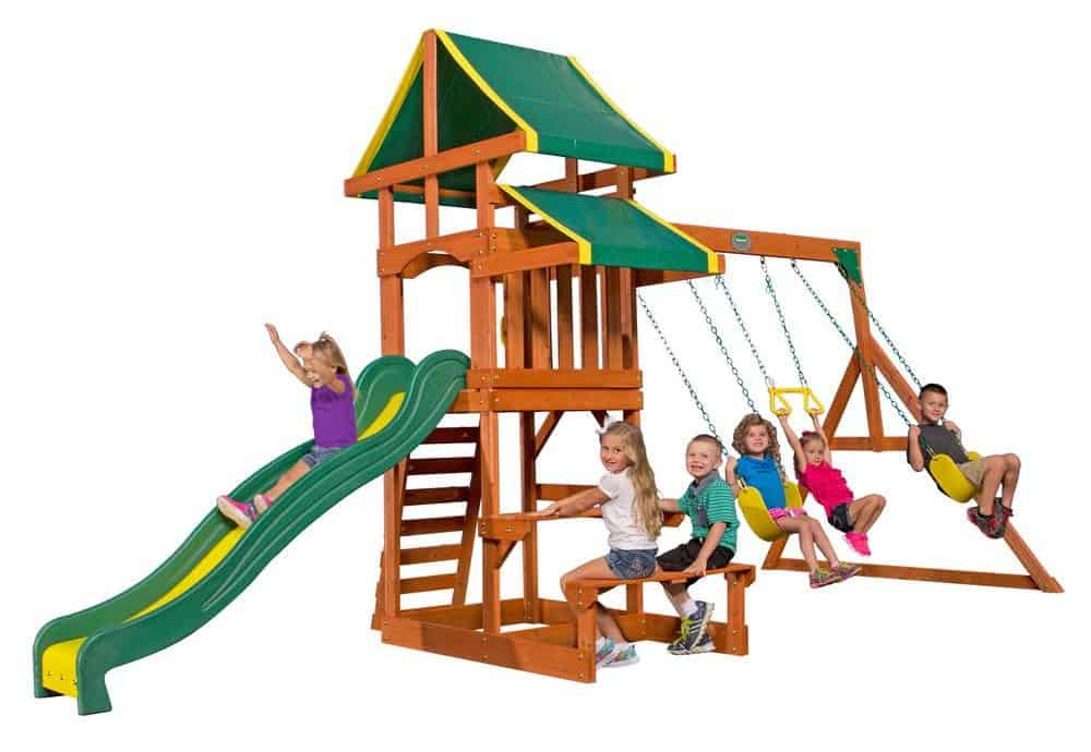 Children's cedar play set with several swings and one, green slide.