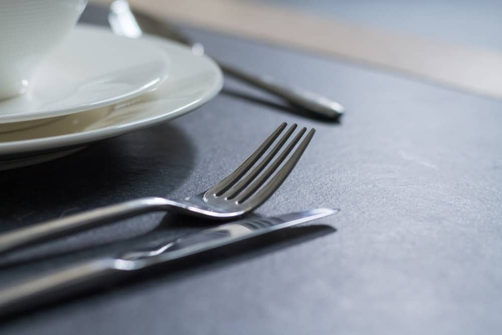 Table fork with knife beside white dining plates on black table.