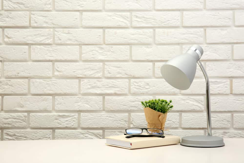 A white table lamp on a study table.