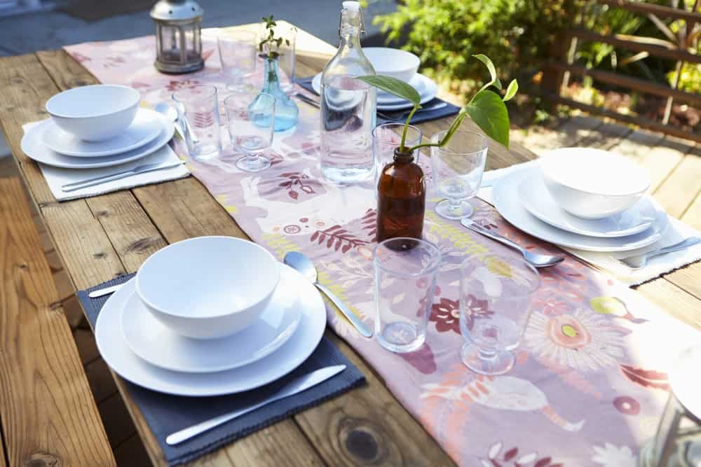 Outdoor table setting with table runner on wooden patio table.
