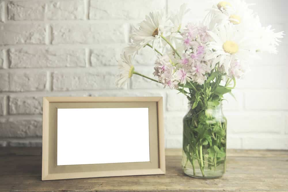 Rectangular, table-top picture frame besides a flower vase.