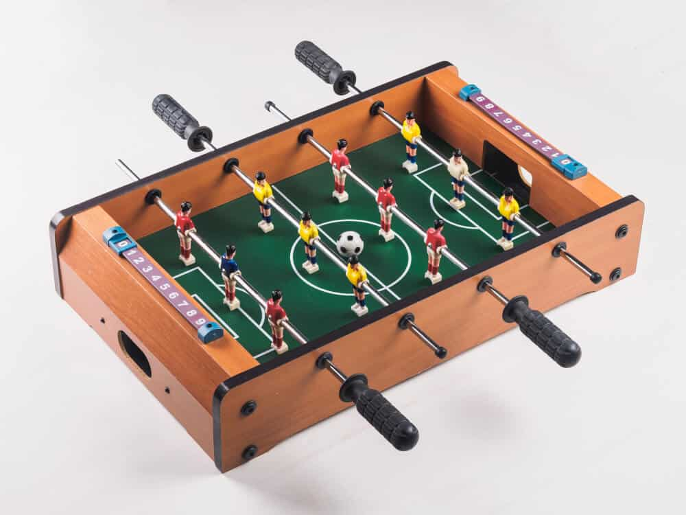 A small, wooden tabletop foosball.