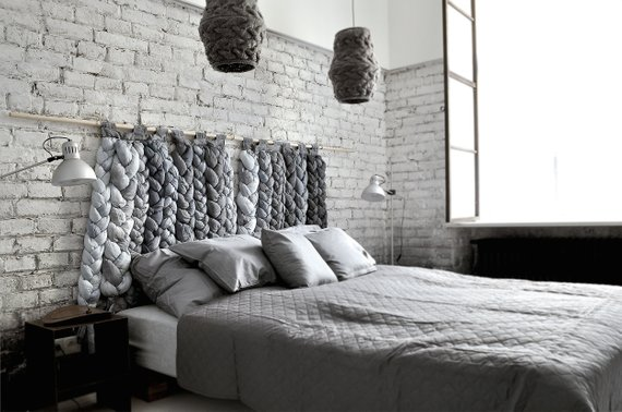Gray Industrial bedroom with gray exposed brick wall, tapestry pendant lighting above the bed, floor lamps, tapestry headboard and gray bedding.