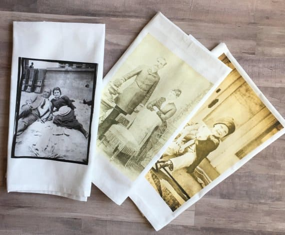 Vintage images printed on tea towels that lie on a wooden background.