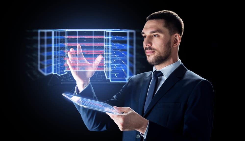 Businessman with transparent tablet PC computer projecting virtual building blueprint.
