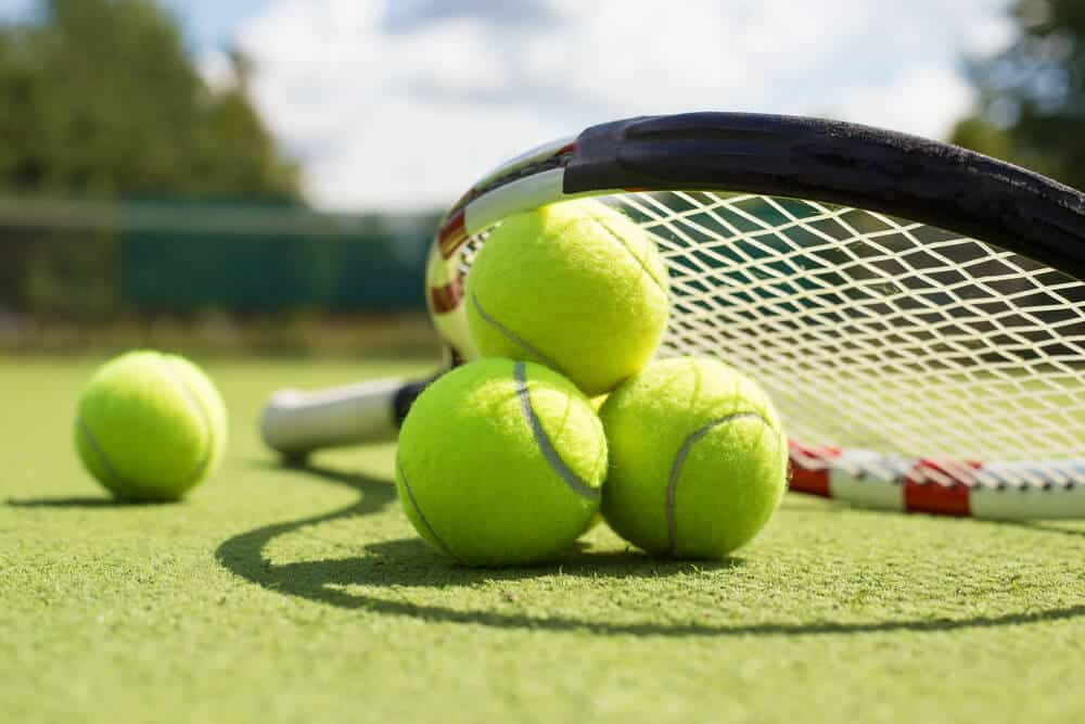 Tennis balls and a racket on the field.