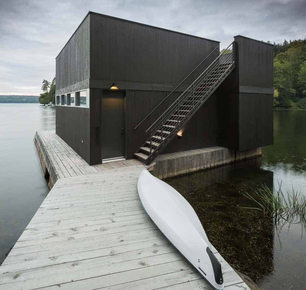 This house features a black exterior with a wooden deck platform and has a wooden walkway.