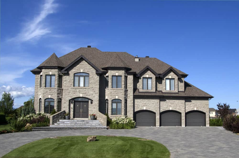 A huge stone house with a touch of light brown tones. It has 3 garages and a spacious area in front, which is a perfect spot for landscaping ideas.