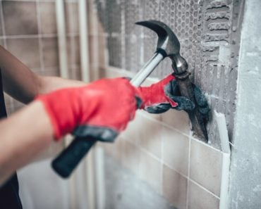 Man with a hammer and chisel removing tiles.