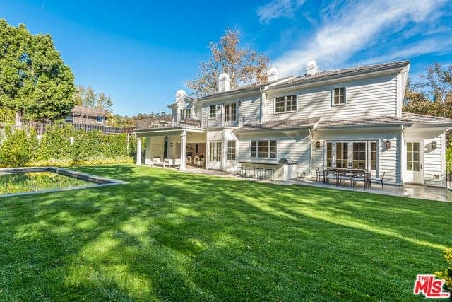 A large home with a sprawling backyard featuring a well-maintained lawn area and a swimming pool on the side.