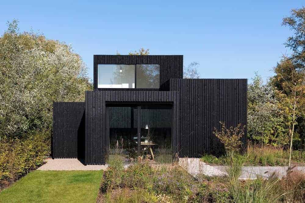 A tiny holiday home featuring a black exterior and has a beautiful garden area.
