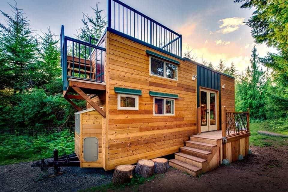 A wooden tiny house with a small upper and lower deck, along with 2 loft sleeping areas.
