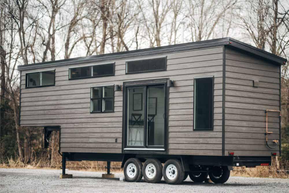 A wooden gray tiny house with glass windows and door.