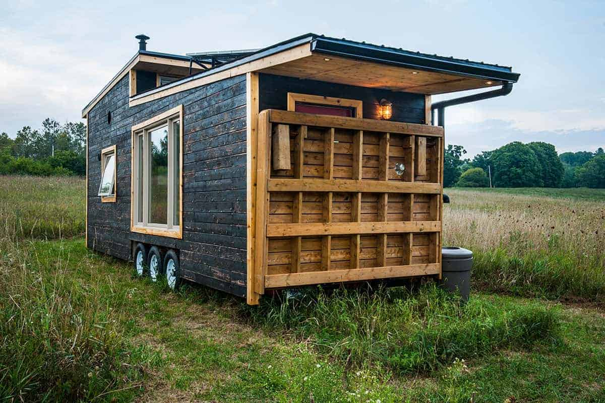A tiny house with a retractable deck and a loft bedroom.