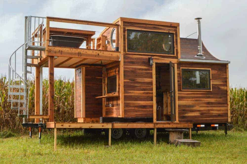 This tiny wooden house boasts a lower and upper deck.