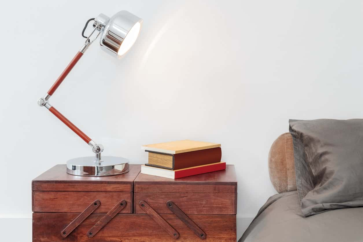 A wooden toolbox with a desk lamp and books on top serves as nightstand alternative in this bedroom.