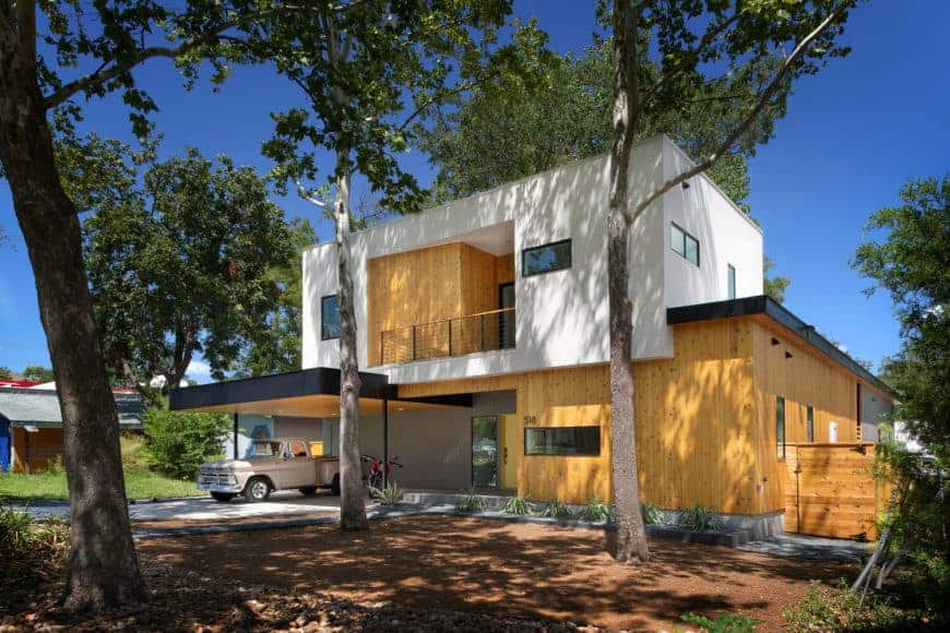Modern house with a wooden exterior and a wide garage with a nice driveway.