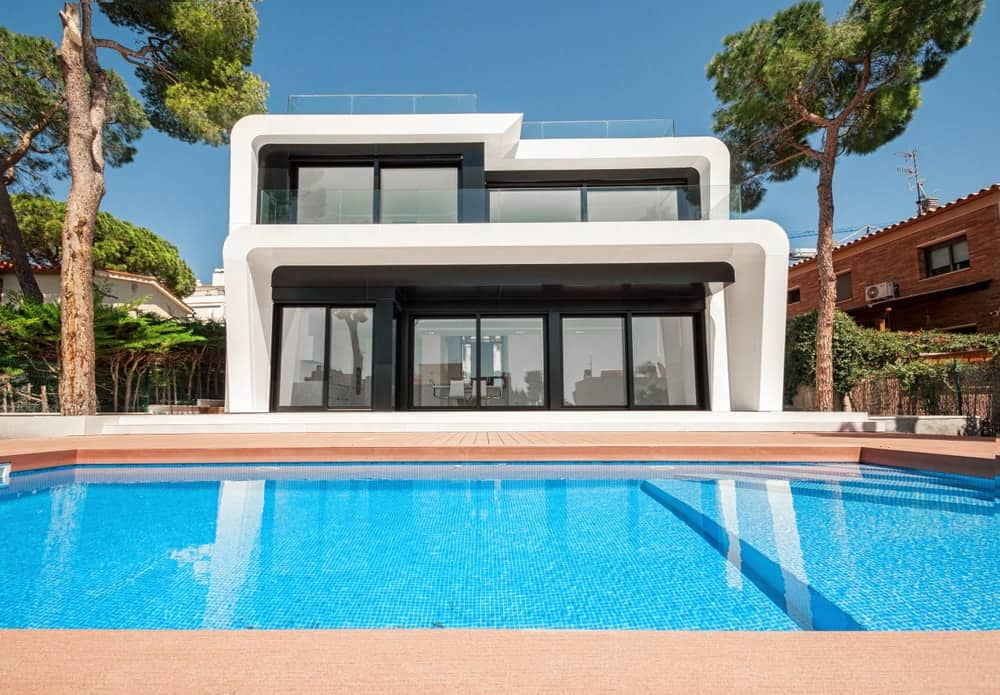 Trendy house with geometric architecture and wide glass windows and outdoor swimming pool.