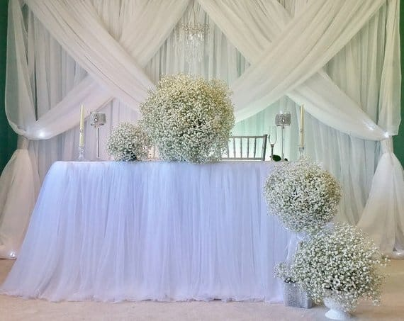 White tulle used as tablecloth on a wedding setting.