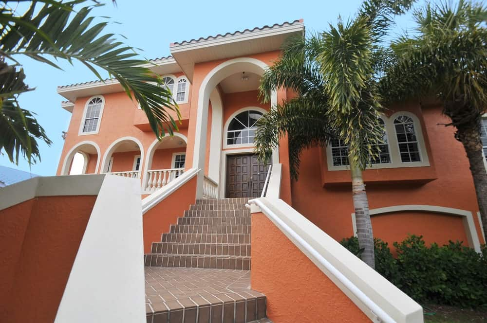 Two-tiered red orange house with white trims, rough stucco exterior, and brick staircase leading to the wooden double front doors under a two-story covered arch.