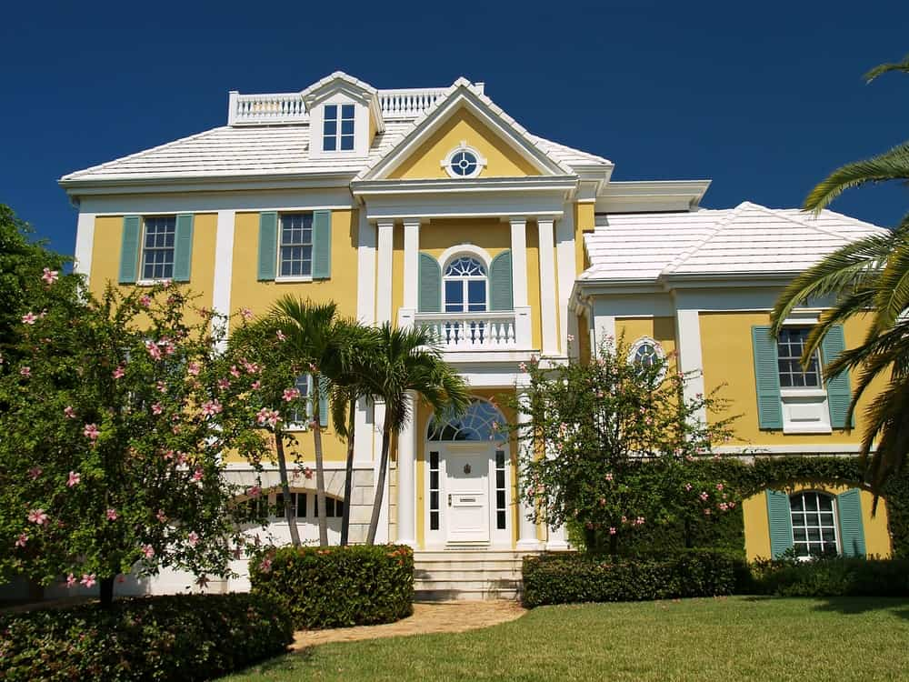 This upscale house looks stunning with a warm yellow facade, dark green shutters, and crisp white outlines.