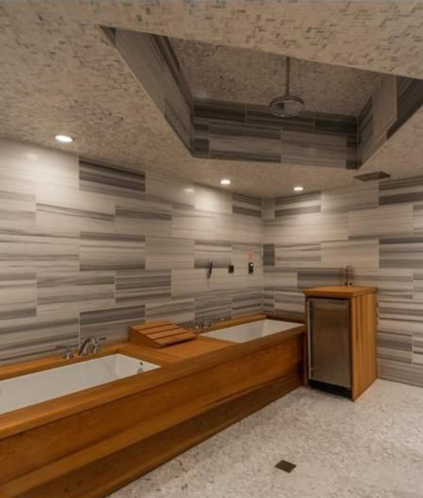 The bathroom offers a deep soaking tub and open shower area along with stylish walls and recessed ceiling lights.