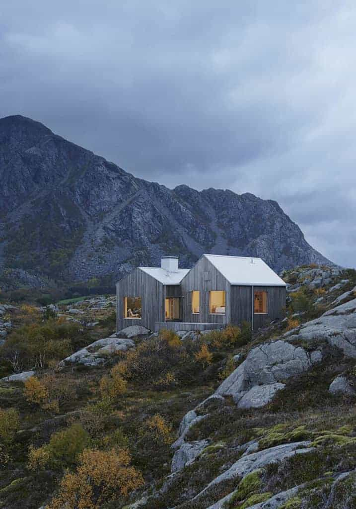 A cottage house with a wooden exterior. It offers a stunning panoramic view of the mountain.