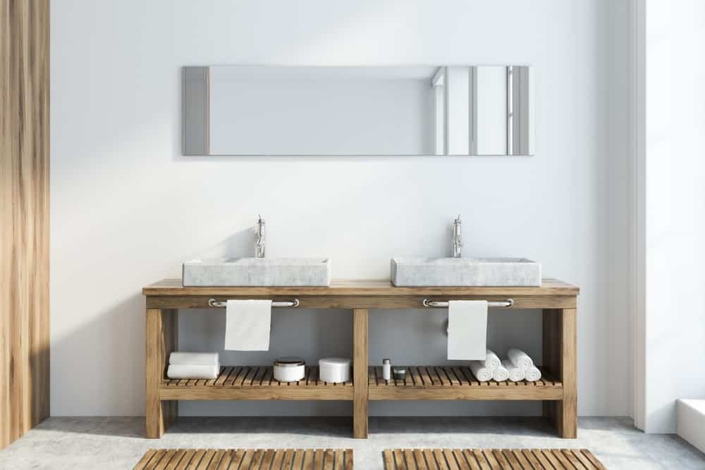A wooden vessel vanity with two partitions.
