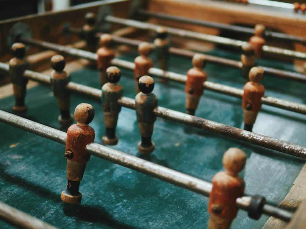 A close-up shot of a wooden, vintage Foosball table.
