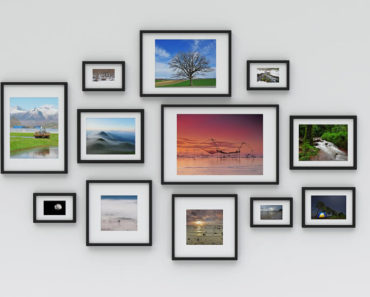 Black picture frames of different shapes and sizes, hanging on a white wall.
