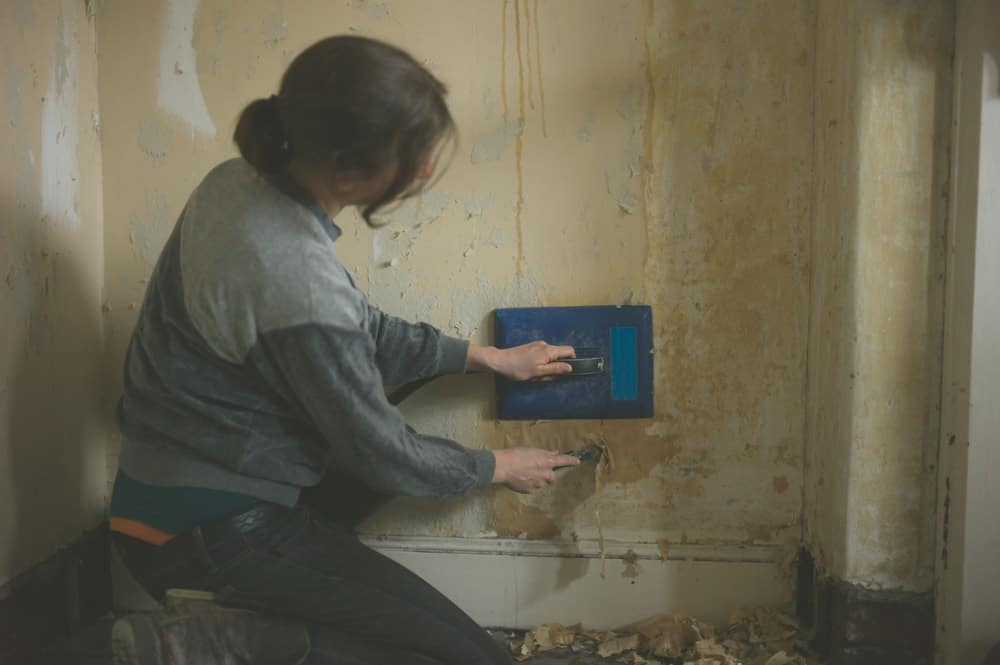 A lady is using a steamer to remove the old wallpaper.