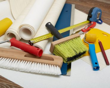 A set of tools that are being used to apply wallpaper.