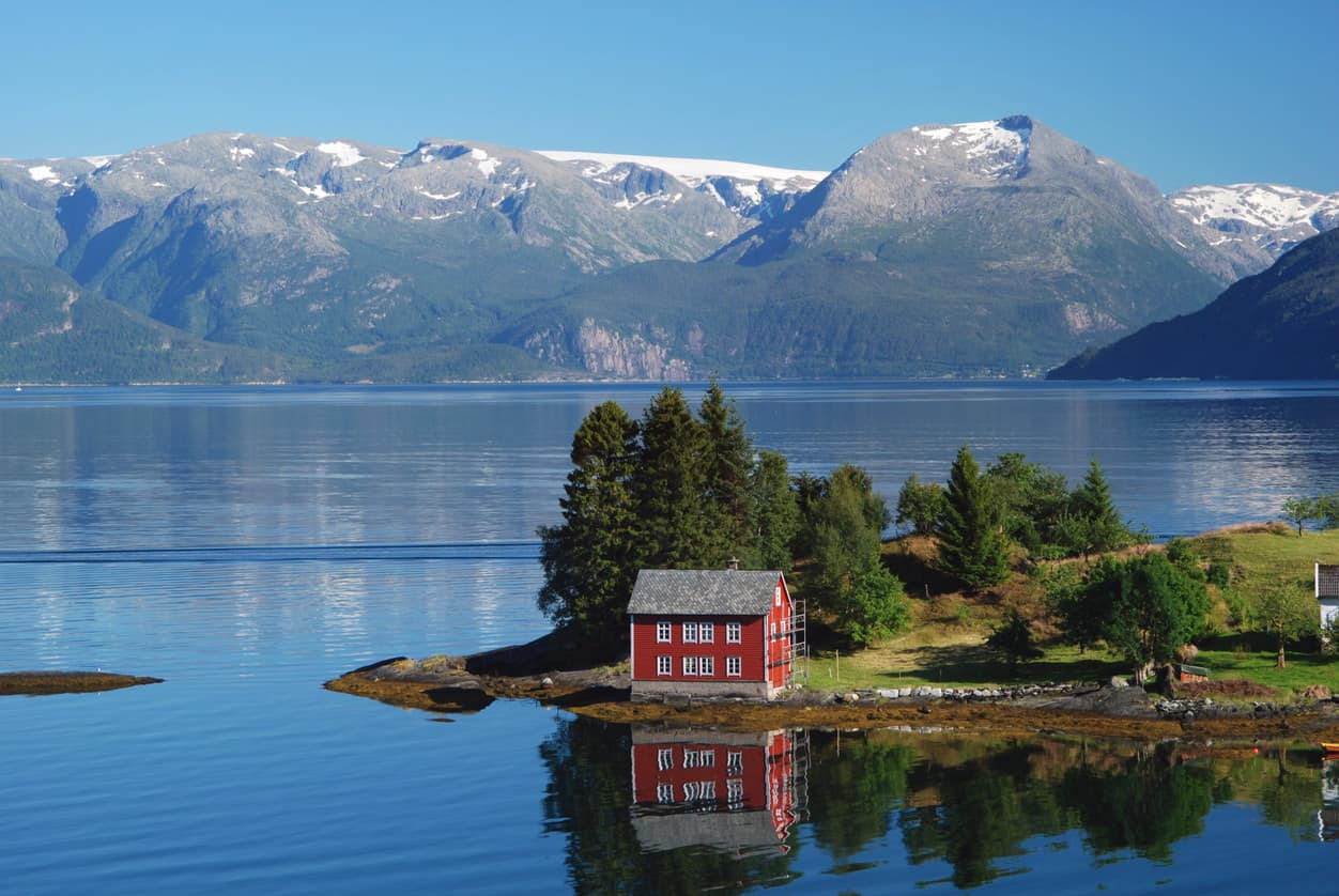 Hardangerfjord in south western Norway in the summer. A red, Norwegian house situated on a small island in the fjord. In the distance the Folgefonna glacier.