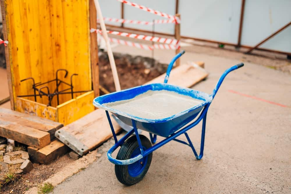 The blue wheelbarrow is being used to transport cement