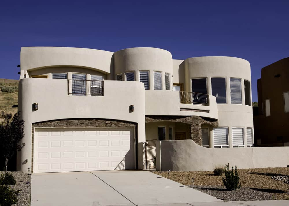 Large two story white adobe house with fenced in front yard and upper balconies.