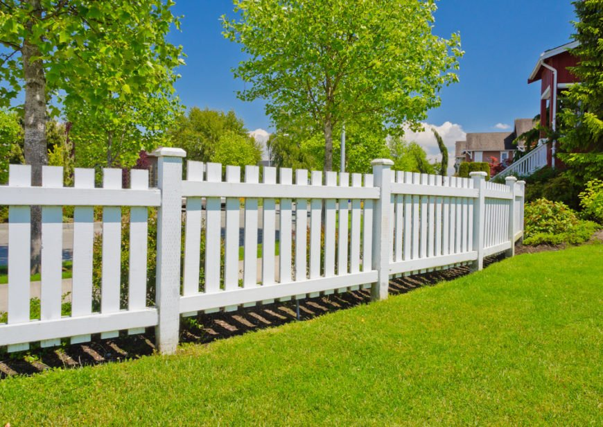 White backyard fence with decorative fence post caps