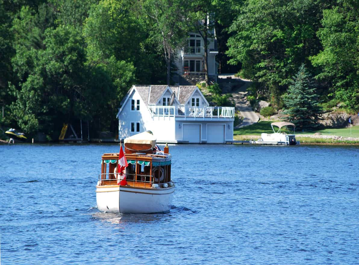 White cottage lake house with boat house